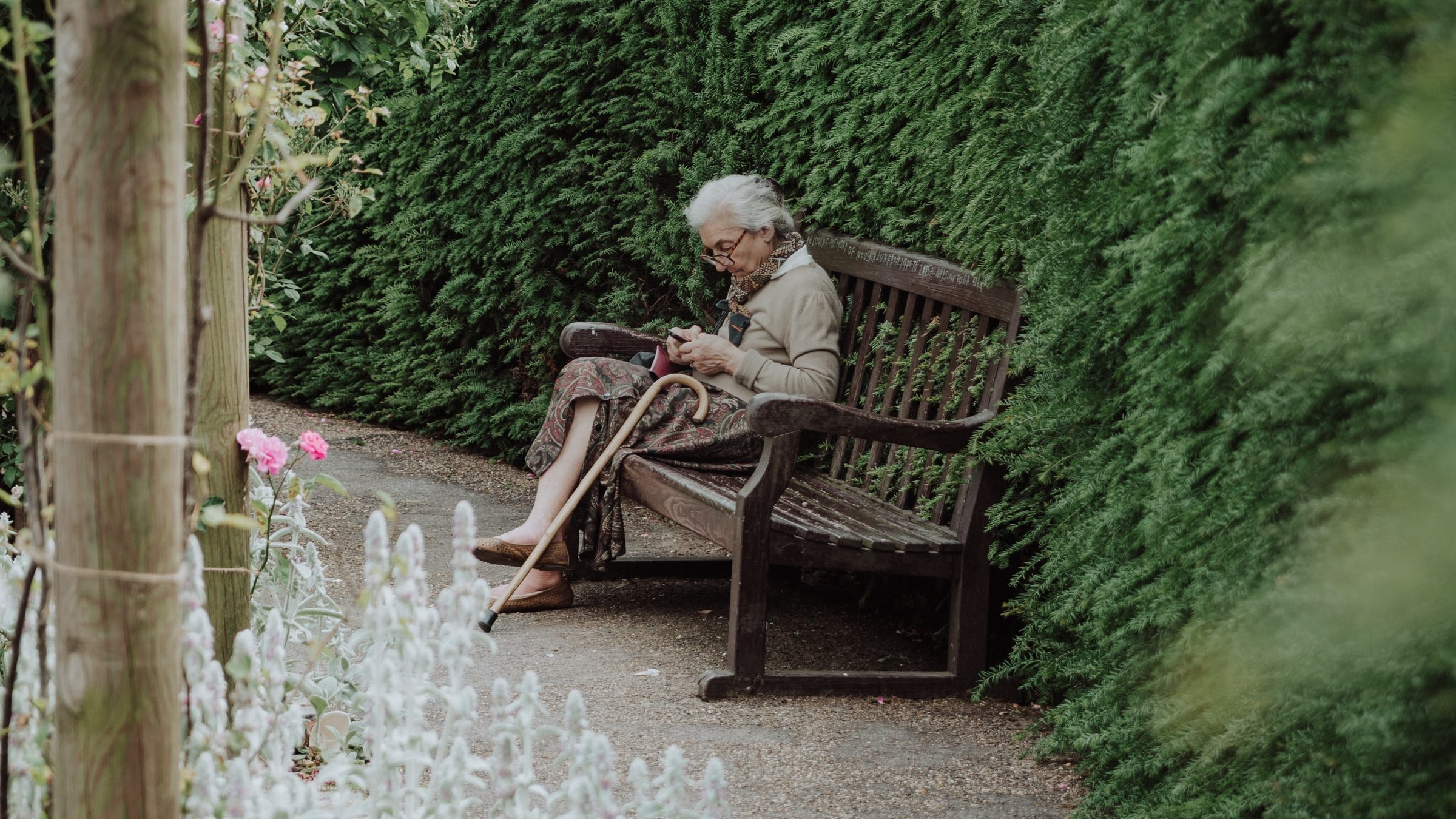 Old lady sitting on a bench with her walking stick